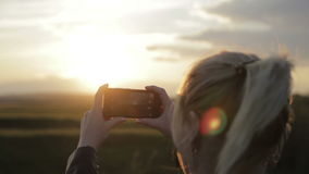 De jonge vrouw neemt de zon aan uw smartphone stock videobeelden