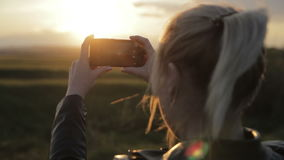 De jonge vrouw neemt de zon aan uw smartphone stock footage