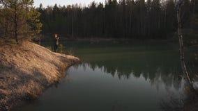 De jonge vrouw neemt foto gebruikend haar telefoon app van een turkoois kleurenmeer in Baltische staten in Letland stock videobeelden