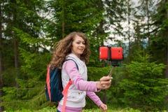 De jonge vrouw neemt selfie met mobiele telefoon in bergen stock afbeelding