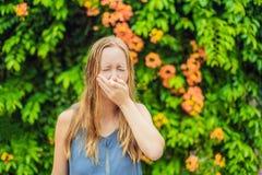 De jonge vrouw niest in het park tegen de achtergrond van een bloeiende boom Allergie voor stuifmeelconcept stock afbeeldingen