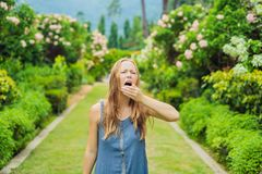 De jonge vrouw niest in het park tegen de achtergrond van een bloeiende boom Allergie voor stuifmeelconcept stock foto's