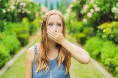 De jonge vrouw niest in het park tegen de achtergrond van een bloeiende boom Allergie voor stuifmeelconcept stock afbeelding