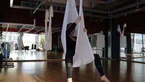 De jonge vrouw oefent klassieke yoga in hangmatsportclub uit stock video
