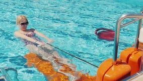 De jonge vrouw oefent op een simulator in de pool uit Actieve rust op verse lucht, activiteit in de toevlucht stock footage