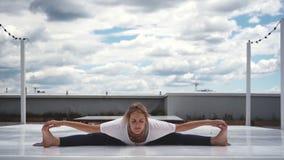 De jonge vrouw oefent yoga uit, zittend in brede hoek vooruit kromming stel stock videobeelden