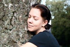 De jonge vrouw omhelst grote boom Stock Fotografie