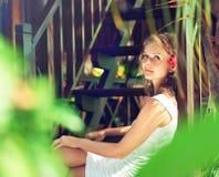 De jonge vrouw, omringde groene installaties stock foto's