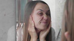 De jonge vrouw onderzoekt haar gezicht voor mimical gezichtsrimpels stock videobeelden