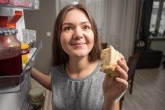 De jonge vrouw onderzoekt de koelkast, mening van koelkast, meisje het eten bij nacht, vrees stock foto