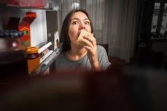 De jonge vrouw onderzoekt de koelkast, mening van koelkast, meisje het eten bij nacht, vrees royalty-vrije stock foto