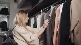 De jonge vrouw onderzoekt prijzen in kledingsopslag op een verkoop stock video