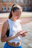 De jonge vrouw onderzoekt telefoon bij sportenstadion stock afbeeldingen