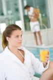 De jonge vrouw ontspant bij zwembad, drinkt sap Stock Afbeelding