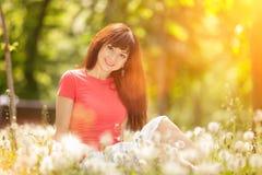 De jonge vrouw ontspant in het park met bloemen De sc?ne van de schoonheidsaard met kleurrijke achtergrond, bomen en bloemen bij  stock foto's