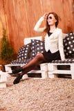 De jonge vrouw ontspant op bank Stock Fotografie