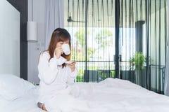De jonge vrouw ontwaakte en het drinken koffie of thee op bed onder sunl Stock Fotografie