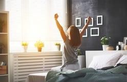 De jonge vrouw ontwaakte in de ochtend in de slaapkamer door windo royalty-vrije stock afbeelding