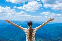 De jonge vrouw op de bovenkant van de heuvel heft op hand op met geniet van en geluk Mooie mening van hemel op hoogste berg Royalty-vrije Stock Afbeeldingen