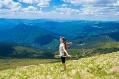 De jonge vrouw op de bovenkant van de heuvel heft op hand op met geniet van en geluk Mooie mening van hemel op hoogste berg Stock Foto
