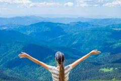 De jonge vrouw op de bovenkant van de heuvel heft op hand op met geniet van en geluk Mooie mening van hemel op hoogste berg Stock Afbeeldingen