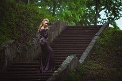 De jonge vrouw op een ladder in het hout royalty-vrije stock afbeeldingen