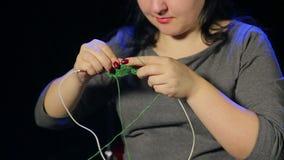 De jonge vrouw op een zwarte achtergrond breit op de naalden van groene draad stock video