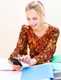 De jonge vrouw op het werk bekijkt de telefoon stock foto's