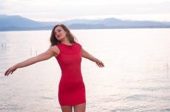De jonge vrouw, op de kusten van Meer Garda, spreidt haar gelukkige wapens uit Stock Fotografie