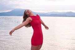 De jonge vrouw, op de kusten van Meer Garda, spreidt haar gelukkige wapens uit Royalty-vrije Stock Foto's