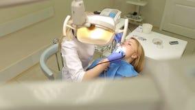 De jonge vrouw op ontvangst bij de tandarts stock videobeelden