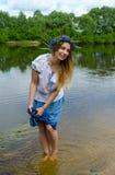 De jonge vrouw op rivierbank drukt natte boord van rok stock afbeelding