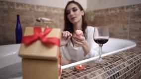 De jonge vrouw opent huidige doos krijgt kleine roze toenam nemend een bad stock video