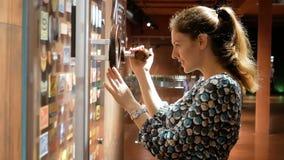 De jonge vrouw overweegt een bank met pictogrammen door een vergrootglas dat zich beweegt Nieuwsgierigheid op het werk Biermuseum stock videobeelden