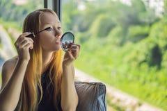 De jonge vrouw past make-upvoorzijde van het venster in schoonheidszitslaapkamer toe Het professionele samenstellingshaar stilere stock foto's