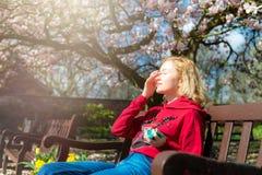 De jonge vrouw past zonnescherm op haar gezicht toe terwijl het zitten op de bank in het park royalty-vrije stock foto