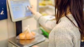 De jonge vrouw in de plantaardige afdeling van een supermarkt weegt mandarijnen stock foto