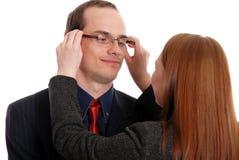 De jonge vrouw probeert op glazen aan de zakenman Stock Fotografie
