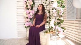 De jonge vrouw in purpere kleding zit op huwelijksbank met bloemen stock video