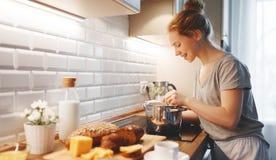 De jonge vrouw in pyjama's bereidt ontbijt in ochtend voor Royalty-vrije Stock Foto