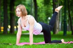 De jonge vrouw rekt zich in het park uit Stock Afbeeldingen
