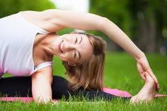 De jonge vrouw rekt zich in het park uit Royalty-vrije Stock Foto