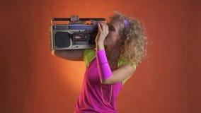 De jonge vrouw in retro uitrusting, zet een cassette in boombox stock videobeelden