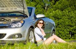 De jonge vrouw roept aan de dienst dichtbij gebroken auto Royalty-vrije Stock Afbeelding