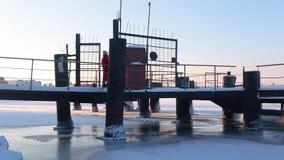 De jonge vrouw in rood lang jasje loopt op snow-covered pijler die zich op bank van bevroren rivier bevinden stock video