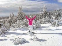 De jonge vrouw in roze jasje, laarzen, ski, polen, beschermende brillen en hoed, dient de lucht in, kijkend erachter gelukkig, sn stock afbeeldingen
