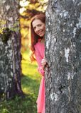 De jonge vrouw in roze kleding, gluurt een boe-geroep achter de boom, met zonnen royalty-vrije stock fotografie