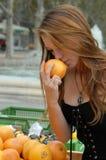 De jonge vrouw ruikt een fruit Stock Foto