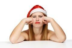De jonge vrouw in santahoed met chagrijnig blik chagrijnig blik kijkt stock fotografie