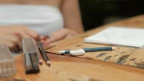 De jonge vrouw scherpt potlood en trekt zitting binnen bij lijst stock video